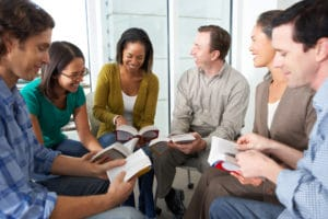 Bible Study Group Reading Together Having A Conversation With Each Other